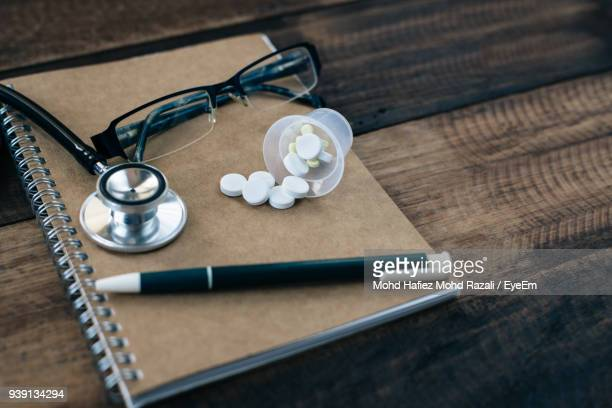 High Angle View Of Stethoscope With Objects On Wooden Table