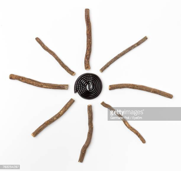 High Angle View Of Stick Arranged In Floral Pattern On White Background