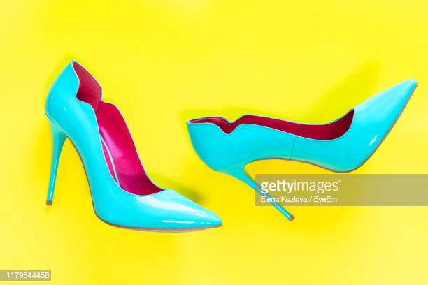 high angle view of stilettos on yellow background - hoge hakken stockfoto's en -beelden