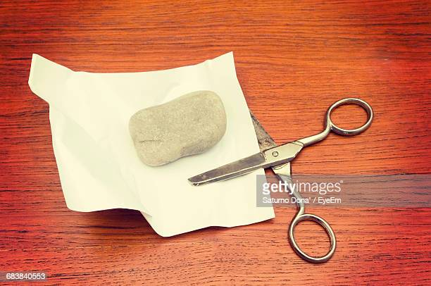 High Angle View Of Stone And Paper With Scissors On Table