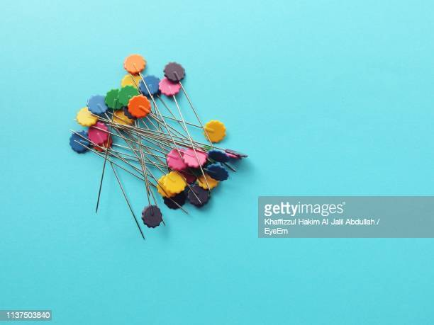 high angle view of straight pins on blue background - shah alam stock photos and pictures