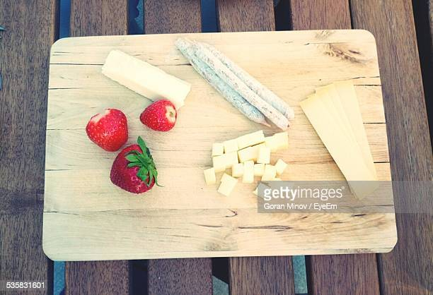 High Angle View Of Strawberry With Cheese And Herb Stick On Cutting Board