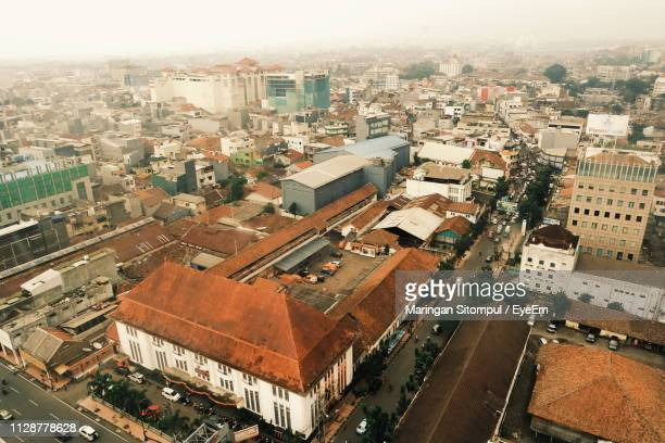 high angle view of street amidst buildings in city - bandung stock pictures, royalty-free photos & images