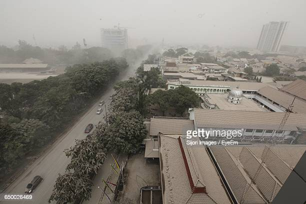 high angle view of street and buildings in foggy weather - surakarta stock photos and pictures