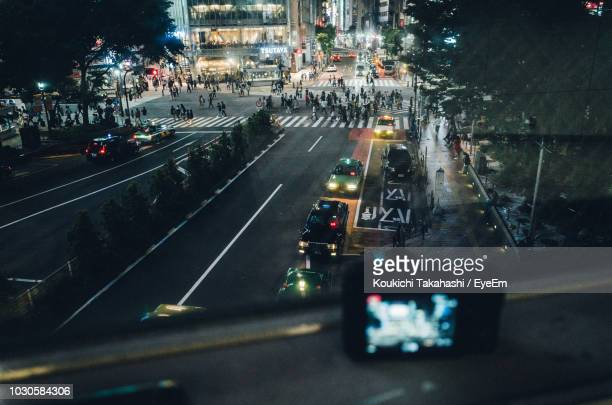 High Angle View Of Street In Illuminated City Seen Through Window At Night