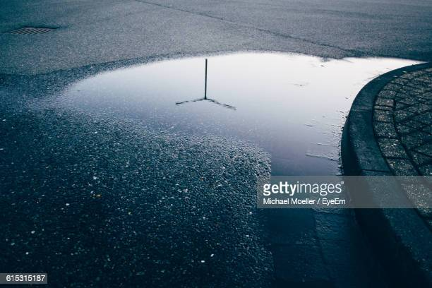 high angle view of street light reflection in puddle - puddle stock pictures, royalty-free photos & images