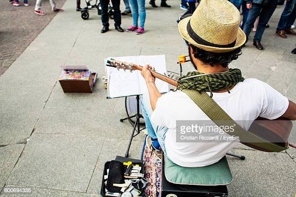 High Angle View Of Street Musician Playing Guitar