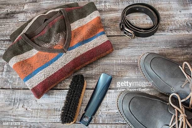 high angle view of striped t-shirt with shoe and brush on table - men fashion stock photos and pictures