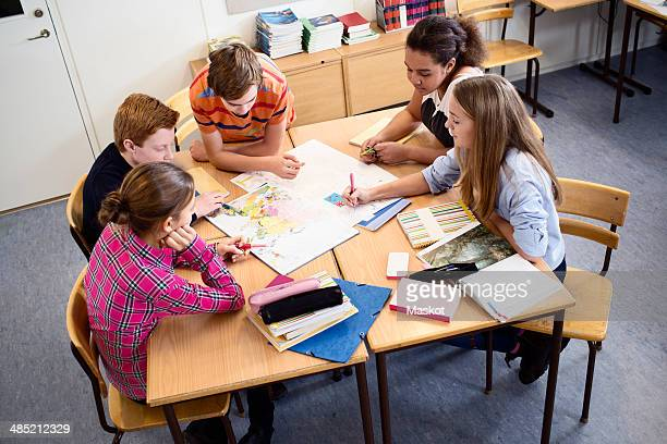 High angle view of students discussing over map in classroom