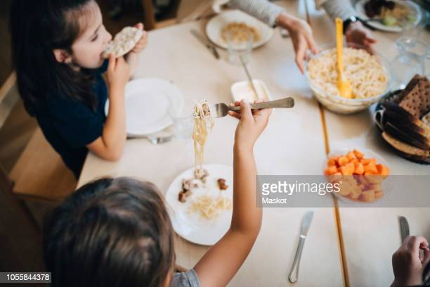 high angle view of students eating lunch while sitting at table in classroom - cantine photos et images de collection