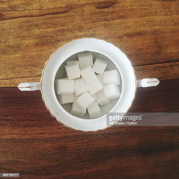 high angle view of sugar cubes in bowl on table - sugar bowl crockery stock photos and pictures