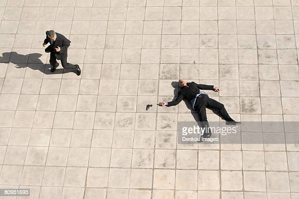 high angle view of suicide scene with businessmen - cadavre photos et images de collection