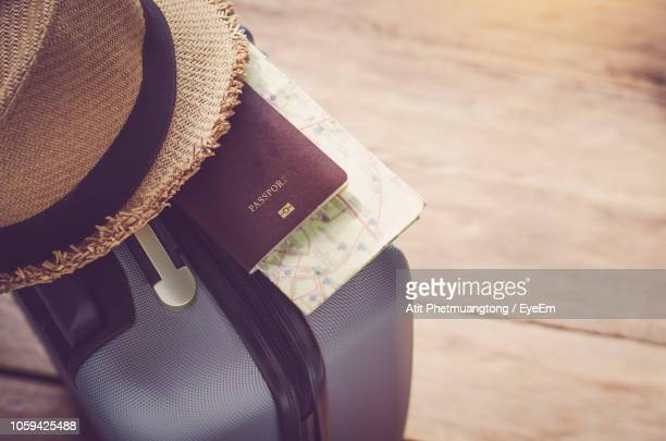 high angle view of suitcase with hat and passport on wooden floor - passeport photos et images de collection