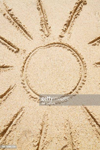 High angle view of sun drawn in sand on the beach