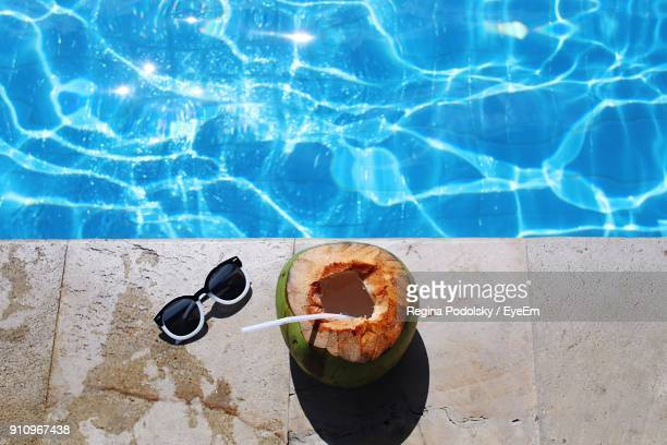 High Angle View Of Sunglasses And Coconut On Swimming Pool