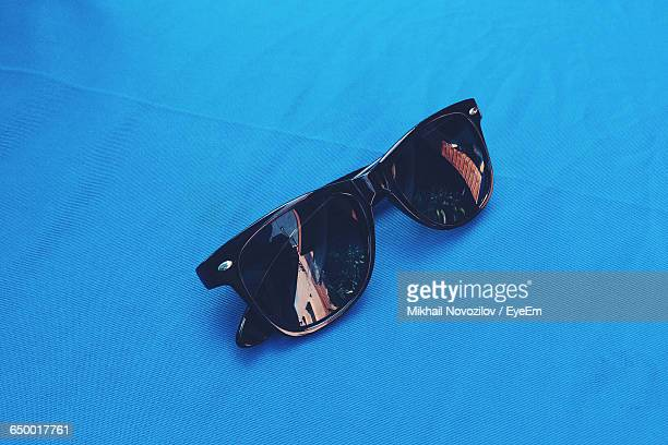 High Angle View Of Sunglasses On Blue Table