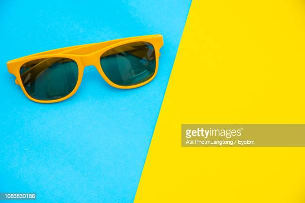 high angle view of sunglasses on colored background - bicolore photos et images de collection
