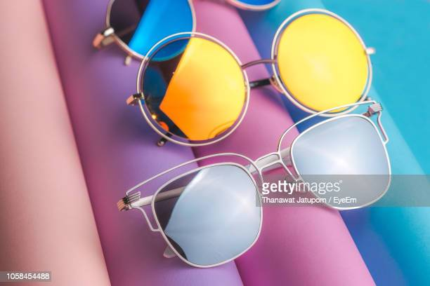 high angle view of sunglasses on table - fashion stock-fotos und bilder