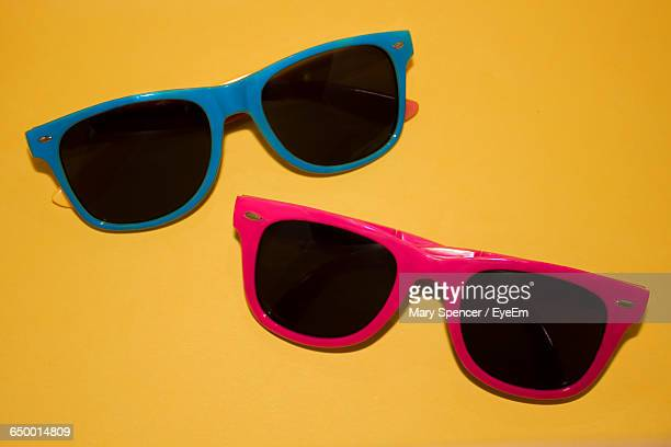 high angle view of sunglasses on yellow table - sunglasses stock photos and pictures