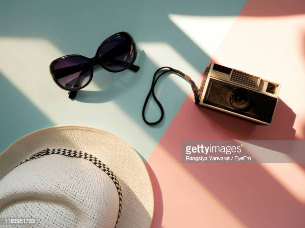 high angle view of sunglasses with camera and hat on table - accessoires stock-fotos und bilder