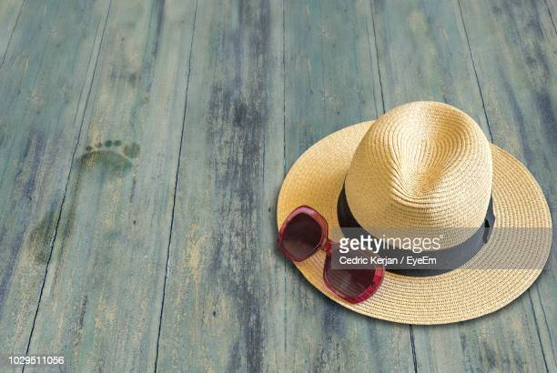 high angle view of sunglasses with hat on wooden table - straw hat stock pictures, royalty-free photos & images