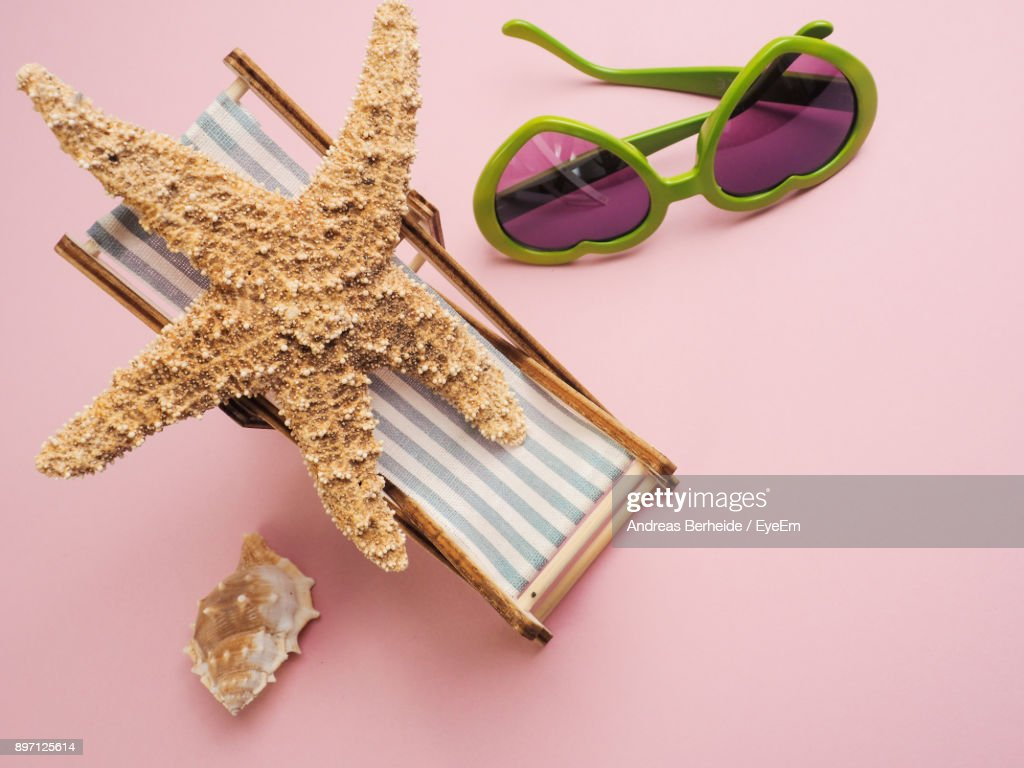 High Angle View Of Sunglasses With Lounge Chair And Starfish Over Pink  Background : Stock Photo