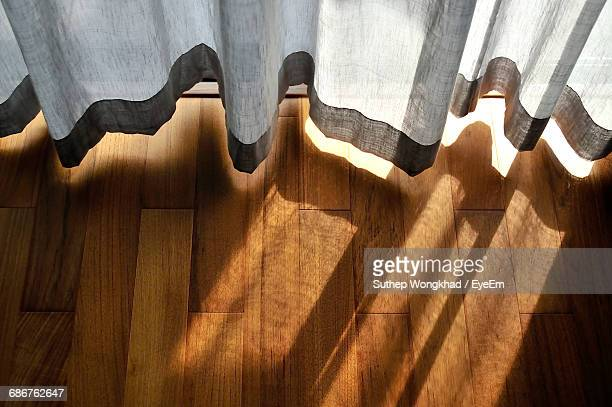 High Angle View Of Sunlight Through Curtain On Hardwood Floor At Home