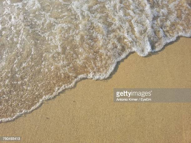 high angle view of surf on beach - riva dell'acqua foto e immagini stock