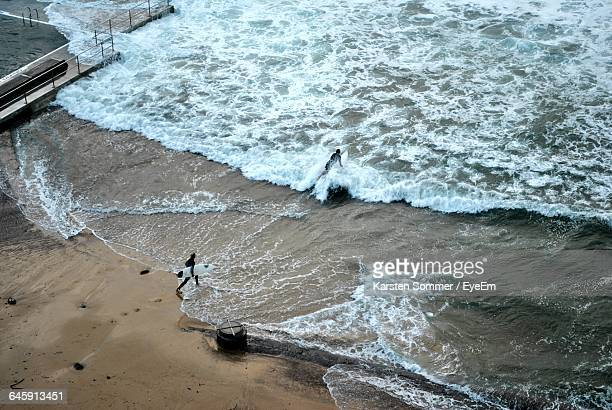 High Angle View Of Surfers On Beach
