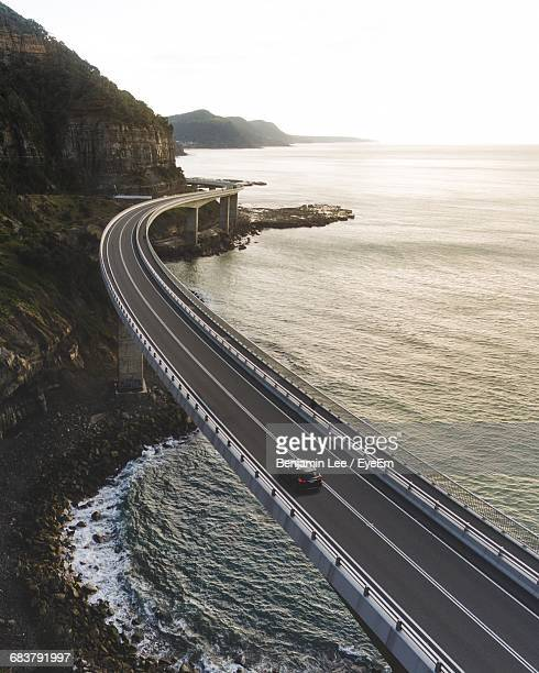 high angle view of suspended highway along the coastline - küstenlandschaft stock-fotos und bilder