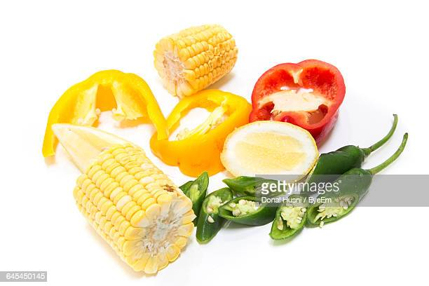 high angle view of sweetcorn and vegetables on white background - green chili pepper stock pictures, royalty-free photos & images