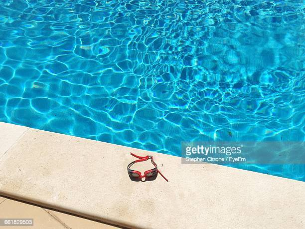 high angle view of swimming goggles on poolside - poolside stock pictures, royalty-free photos & images