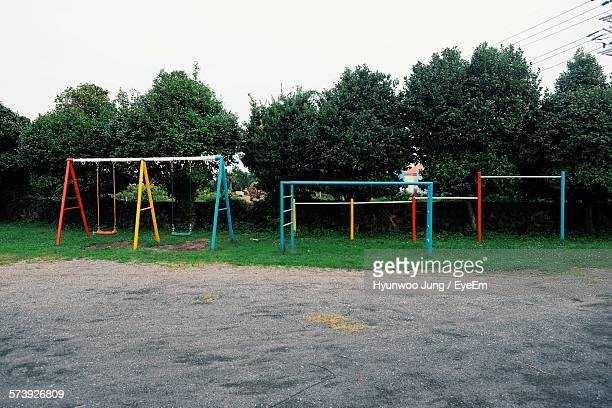 high angle view of swings against trees at park - leisure equipment stock pictures, royalty-free photos & images
