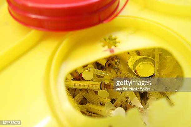 High Angle View Of Syringes In Yellow Disposal Container