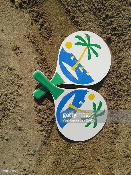 high angle view of table tennis rackets on sand at beach - racquet stock pictures, royalty-free photos & images