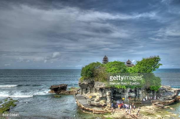 high angle view of tanah lot by sea against cloudy sky - tanah lot stock pictures, royalty-free photos & images