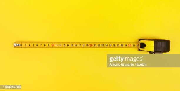 high angle view of tape measure on yellow background - tape measure stock pictures, royalty-free photos & images