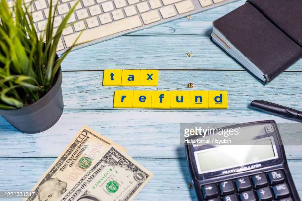 high angle view of tax and refund text on table - tax stock pictures, royalty-free photos & images