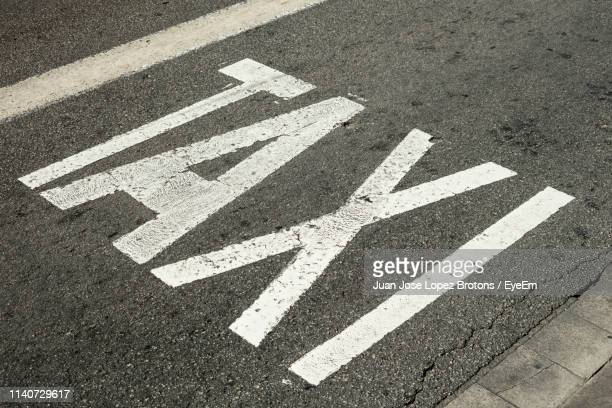 high angle view of taxi sign on road - single word stock pictures, royalty-free photos & images