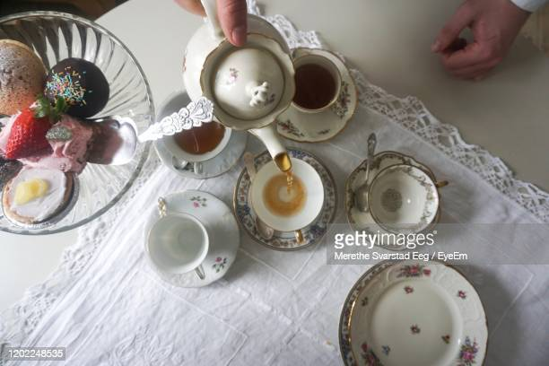 high angle view of tea and cakes on table - saucer stock pictures, royalty-free photos & images