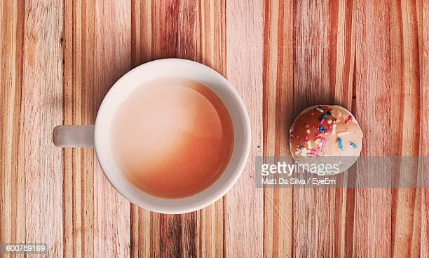 High Angle View Of Tea And Cookie On Wooden Table