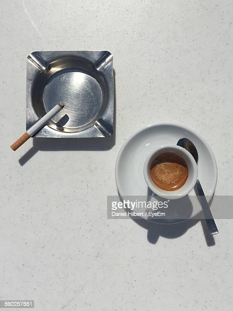 High Angle View Of Tea Cup And Cigarette On Table