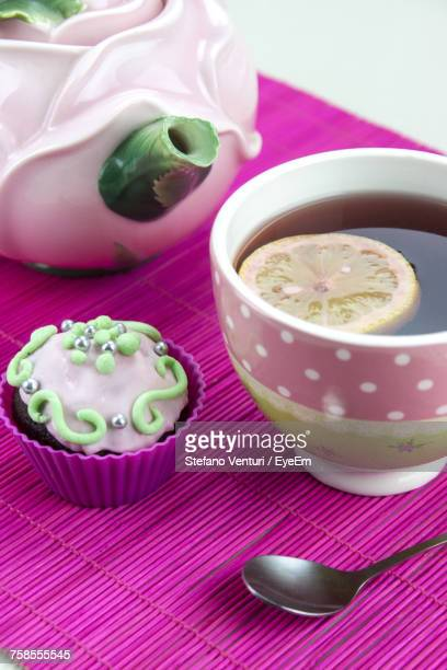 High Angle View Of Tea Cup With Cupcake On Table