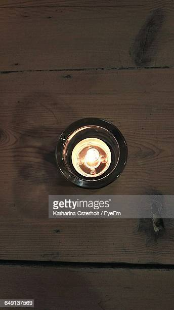 High Angle View Of Tea Light Candle On Wooden Table