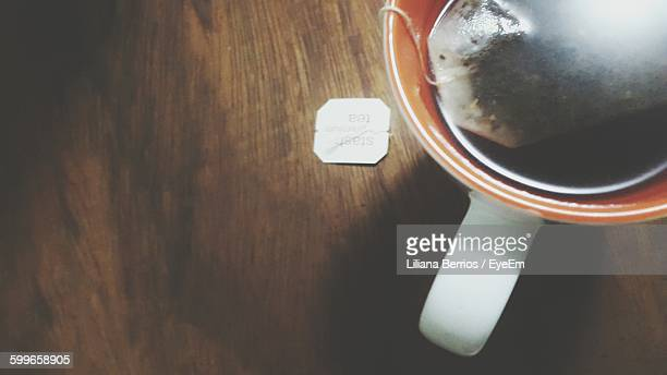 High Angle View Of Teabag In Cup On Wooden Table