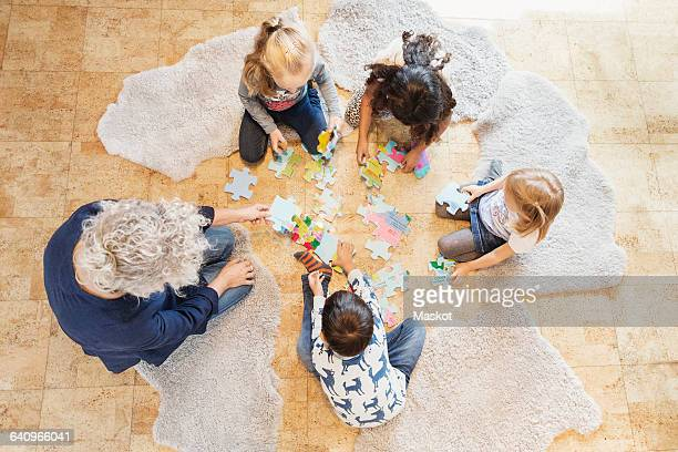 High angle view of teacher and children playing jigsaw puzzle