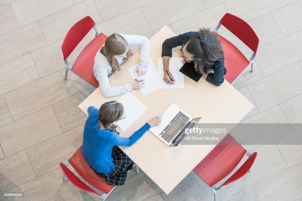 High angle view of teacher helping students do research : Stock Photo