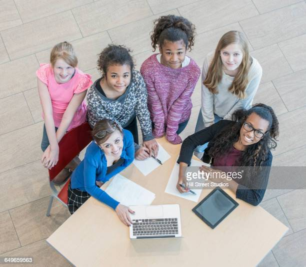 High angle view of teacher helping students do research