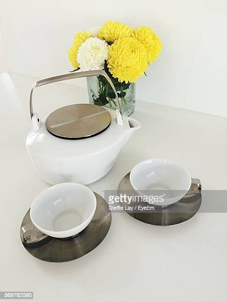 High Angle View Of Teapot And Cups With Flower Vase On White Table
