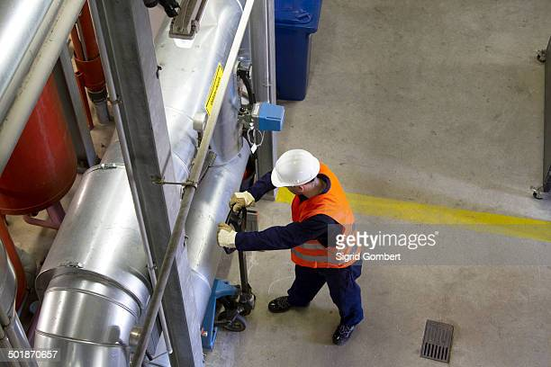 High angle view of technician with pallet trolley in power station